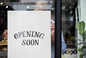 Man with opening soon sign