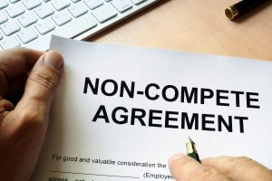 Man signing non-compete agreement