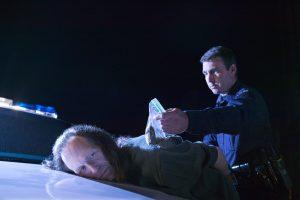 Police officer making drug arrest.